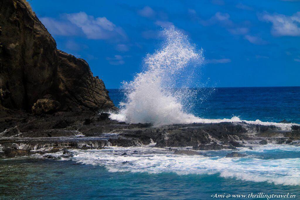 Waves lashing out at the cliff dividing Koka beach