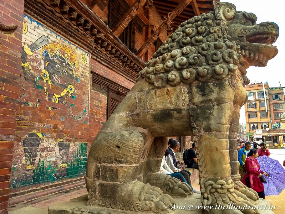 The female lion with the wall art of Kali in the backdrop - Patan