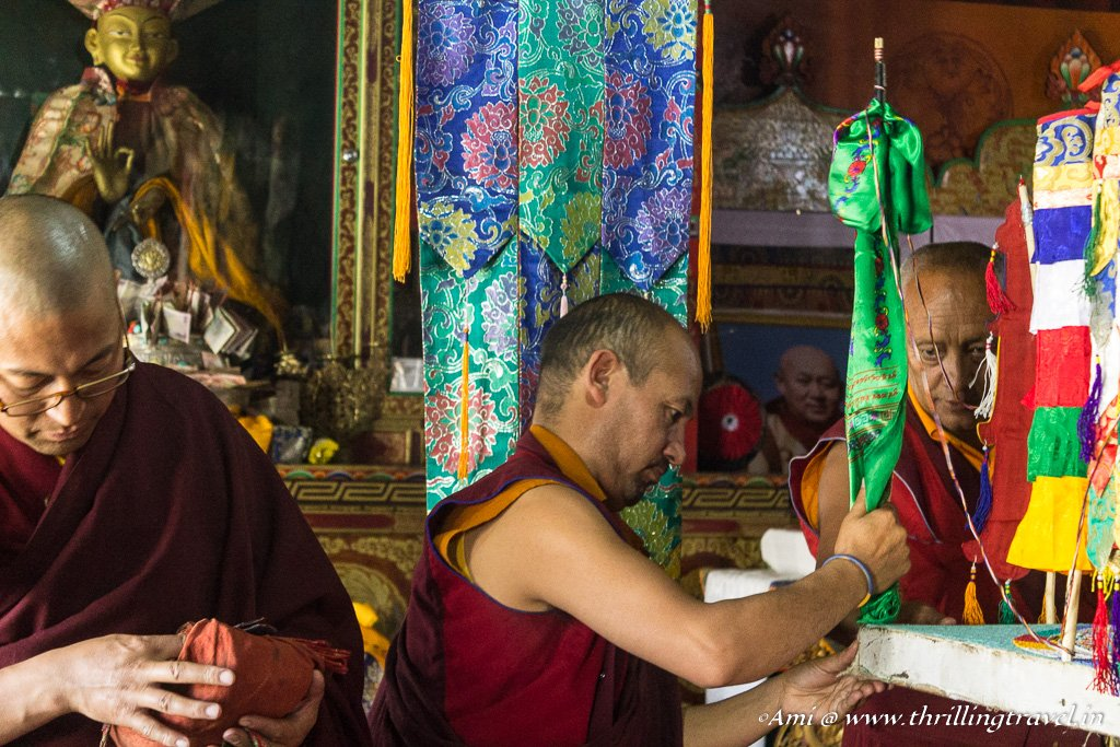 The Monk adding Dattar Flags around the Mandala design