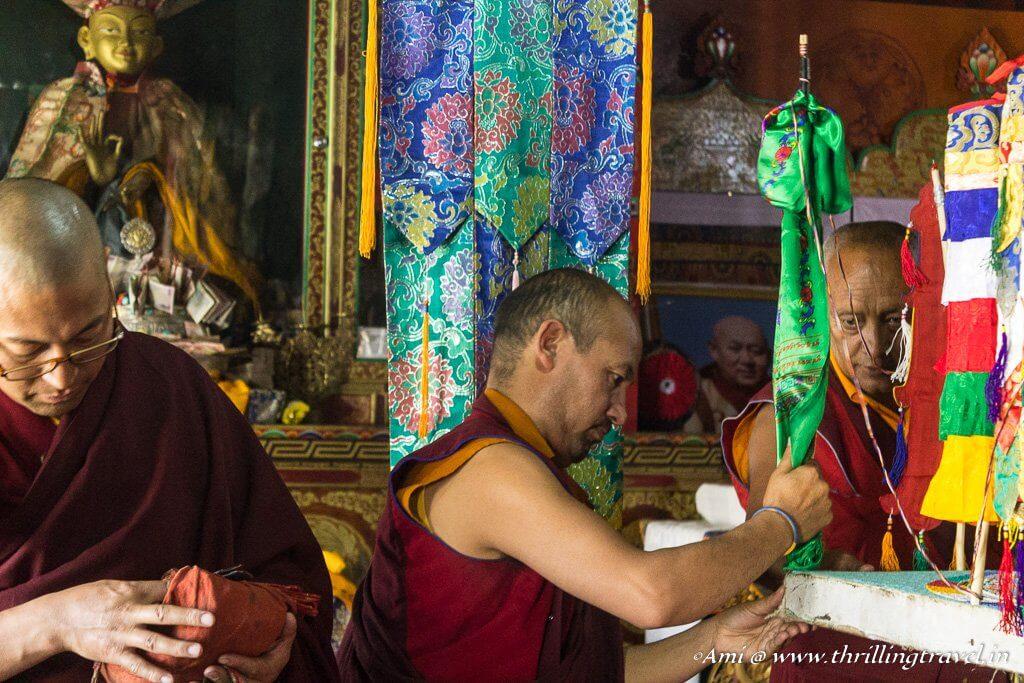 The Monk adding Dattar Flags around the Mandala design