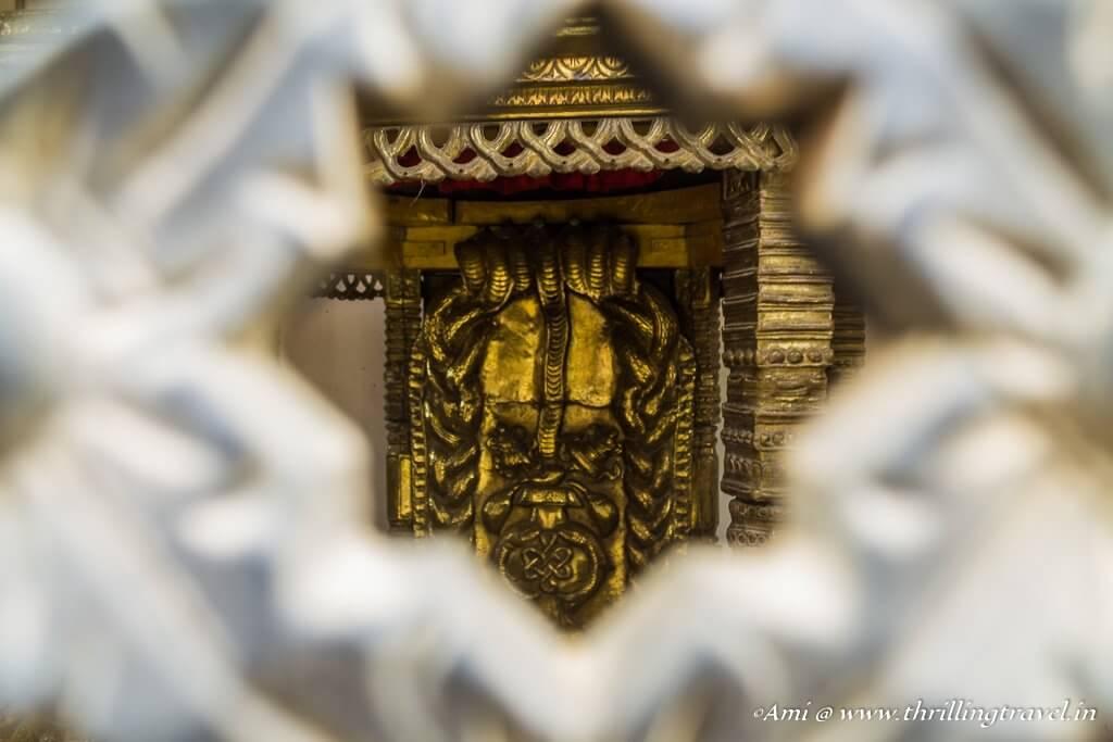 Naga deity through the holes of the temple