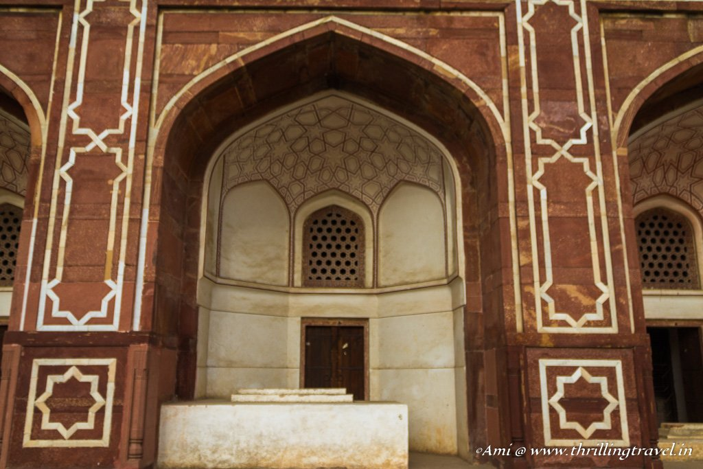 One of the white arched cells at the base of the main Humayun's tomb