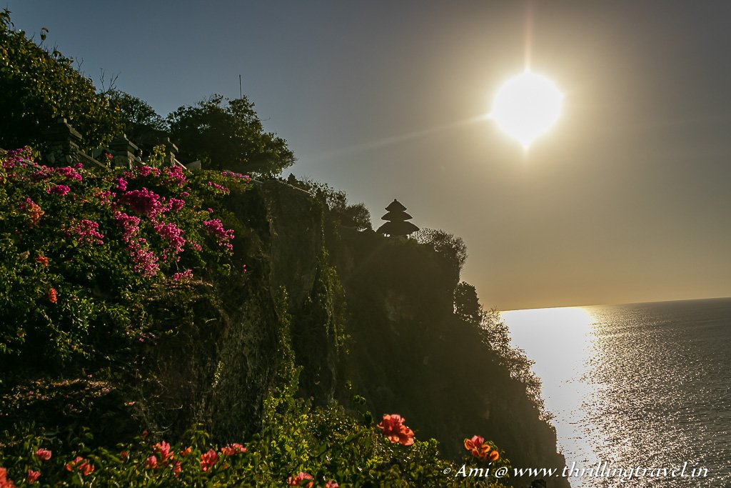 Sunset that lights up the bougainvillea and casts the perfect silhouette of Uluwatu Temple