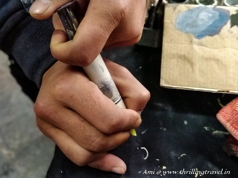 Artist using a syringe to create a 3D outline